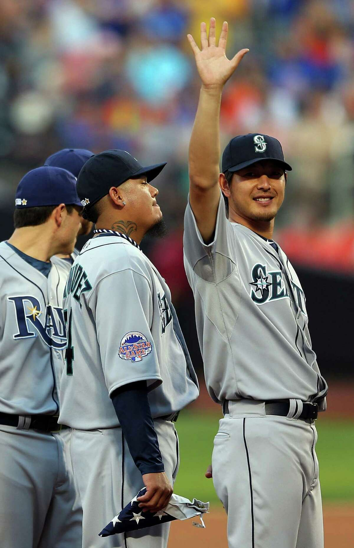 American League All-Star Hisashi Iwakuma, of the Seattle Mariners, waves as Felix Hernandez stands nearby during the 84th MLB All-Star Game on July 16, 2013, at Citi Field in Queens, N.Y.