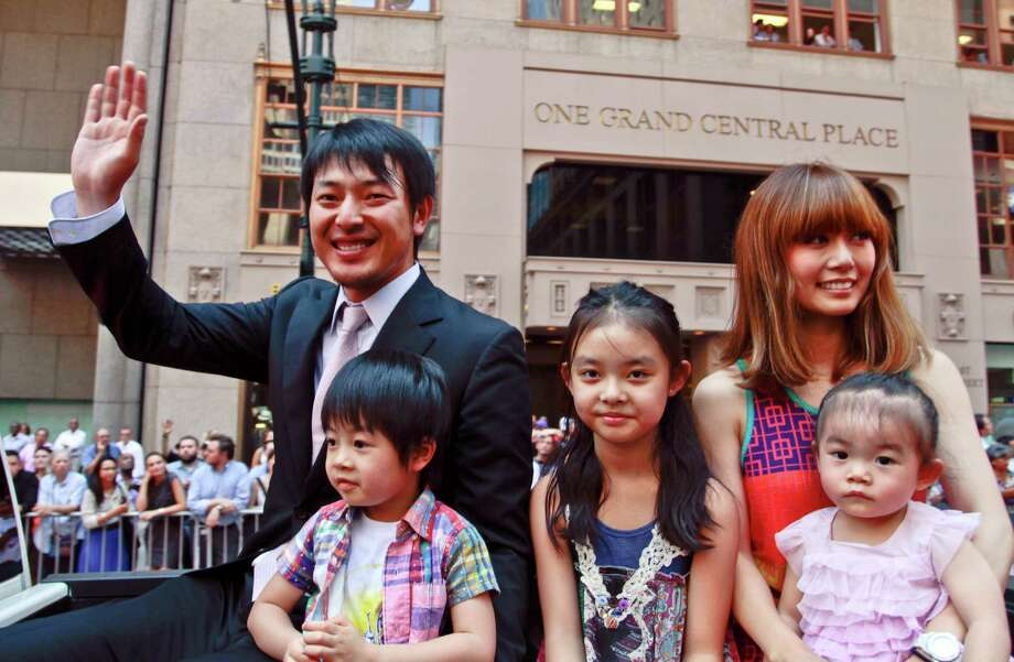 Seattle Mariners pitcher Hisashi Iwakuma waves to cheering fans as he rides with his family during a parade of baseball All-Stars down a red carpet along 42nd Street on July 16, 2013, in New York. Photo: AP