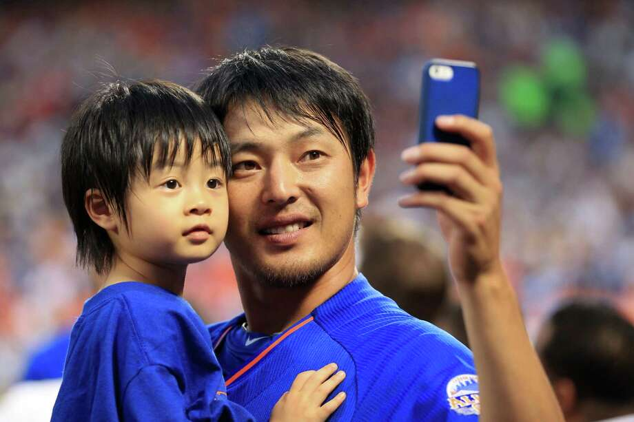 American League All-Star Hisashi Iwakuma, of the Seattle Mariners, takes a picture with his son during the Home Run Derby at Citi Field on Monday, July 15, 2013, in Queens, N.Y. Photo: Paige Calamari, MLB Photos Via Getty Images / 2013 Major League Baseball Photos