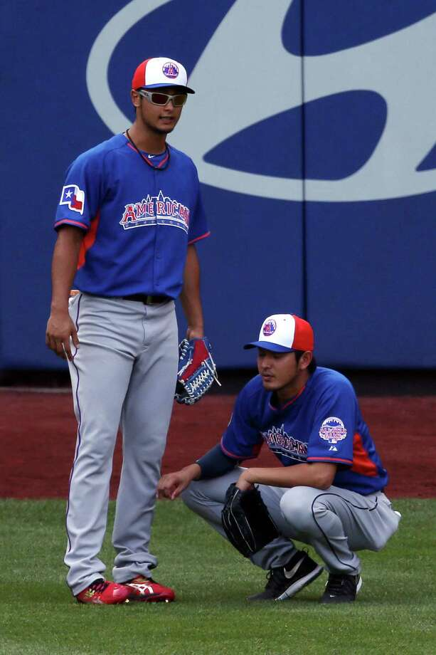 American League All-Stars Yu Darvish, of the Texas Rangers, and Hisashi Iwakuma of the Seattle Mariners, right, shag fly balls in the outfield before the 84th MLB All-Star Game on July 16, 2013 at Citi Field in Queens, N.Y. Photo: Bruce Bennett, Getty Images / 2013 Getty Images
