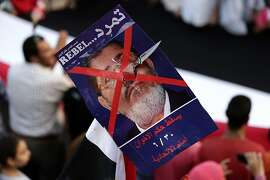 "FILE - In this Monday, July 1, 2013 file photo, an opponent of Egypt's Islamist President Mohammed Morsi holds a poster with Arabic that reads, ""Tamarod, down with the Muslim Brotherhood regime, 6/30, in front of Itihadeya,"" during a protest outside the presidential palace, in Cairo, Egypt. The removal of Mohammed Morsi by the military was the culmination of nearly a year of acrimonious relations between the armed forces chief Gen. Abdel-Fattah el-Sissi and Egypt's first freely elected _ and first civilian _ president. According to a series of interviews by The Associated Press with defense, security, intelligence and Muslim Brotherhood officials, the two clashed over policies toward protests in the streets and over Islamic militants in Sinai, with el-Sissi bristling at Morsi's orders and at times even ignoring them. Each believed the other was conspiring to remove him. And when an activist group began working toward massive protests to remove Morsi, the military early on lent its help from behind the scenes.  (AP Photo/Hassan Ammar, File)"