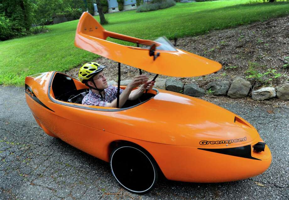Kennis Koldewyn, 41, of Brookfield, Conn., pulls down the hood of the Greenspeed Glyde Velomobile that he uses to commute to his job in Newtown. Photo: Carol Kaliff / The News-Times