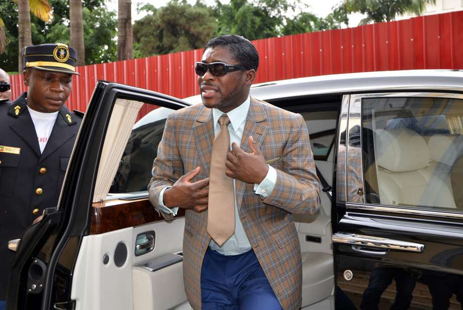 A picture taken on June 25, 2013 shows Teodorin Nguema Obiang (R), the son of Equatorial Guinea's president Teodoro Obiang and the country's vice-president in charge of security and defence, arriving at Malabo's Cathdral to celebrate his 41st birthday. AFP PHOTO / JEROME LEROY