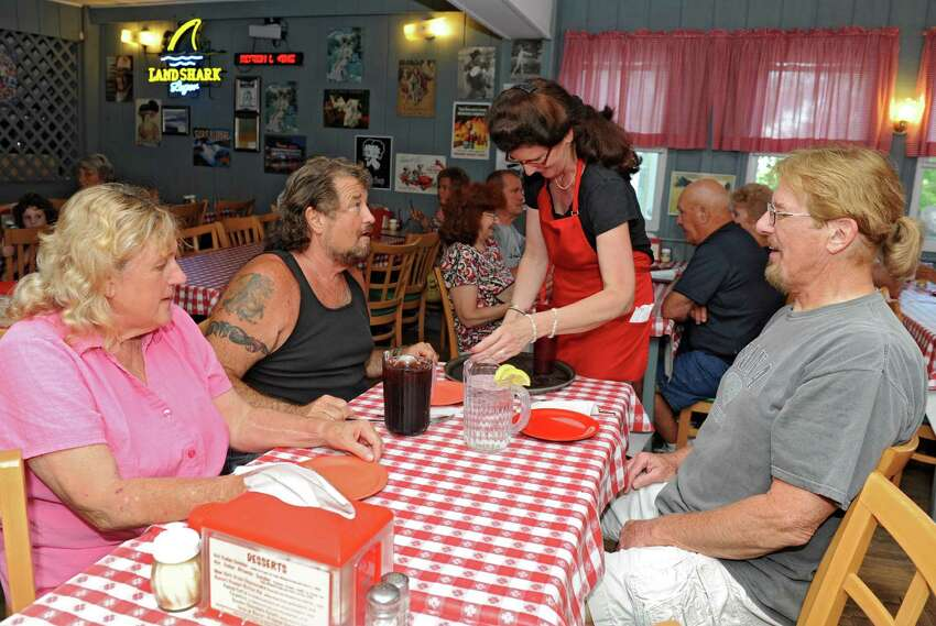 Waitress Suzie Kelly takes the orders from Kate and Denny Stewart of West Sand Lake and Rich Pearsall of Clifton Park, right, at Kay's Pizza on Thursday, July 11, 2013 in Averill Park, N.Y. The Stewarts have been coming to the restaurant for over forty years. (Lori Van Buren / Times Union)