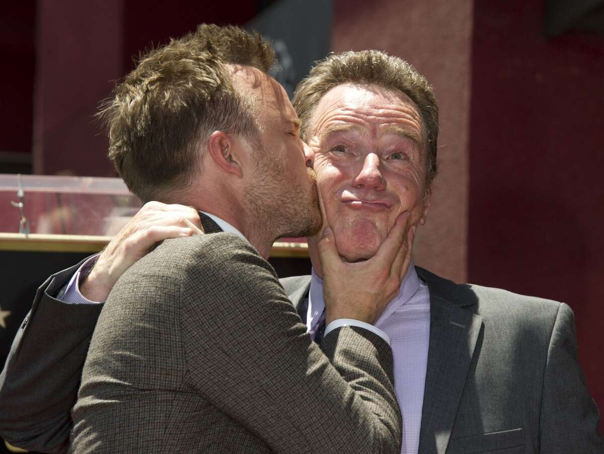"""Actor Aaron Paul (L) kisses Bryan Cranston at Cranston's star presentation ceremony on the Hollywood Walk of Fame, July 16, 2013 in Hollywood, California. Paul and Cranston co-star in the television series """"Breaking Bad."""" AFP PHOTO / ROBYN BECKROBYN BECK/AFP/Getty Images"""