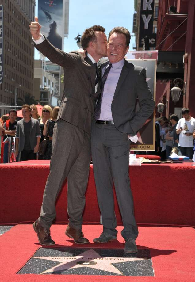Aaron Paul, left, kisses Bryan Cranston atop his new star on the Hollywood Walk of Fame on Tuesday, July 16, 2013 in Los Angeles. (Photo by John Shearer/Invision for AMC/AP Images)