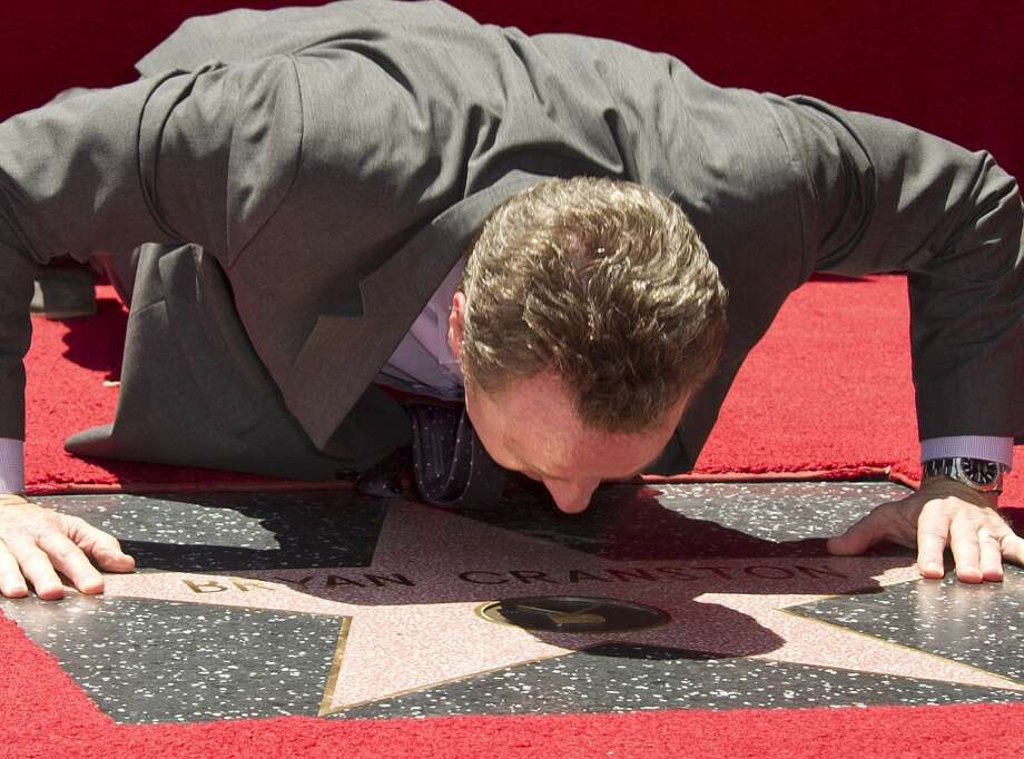 Actor Bryan Cranston gets up close with his newly unveiled star at the star presentation ceremony on the Hollywood Walk of Fame, July 16, 2013 in Hollywood, California.  AFP PHOTO / ROBYN BECKROBYN BECK/AFP/Getty Images