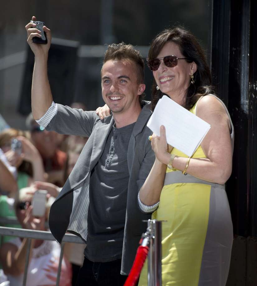 Actors Frankie Muniz (C) and Jane Kaczmarek (R) attend the star presentation ceremony for actor Bryan Cranston on the Hollywood Walk of Fame , July 16, 2013 in Hollywood, California.  AFP PHOTO / ROBYN BECKROBYN BECK/AFP/Getty Images