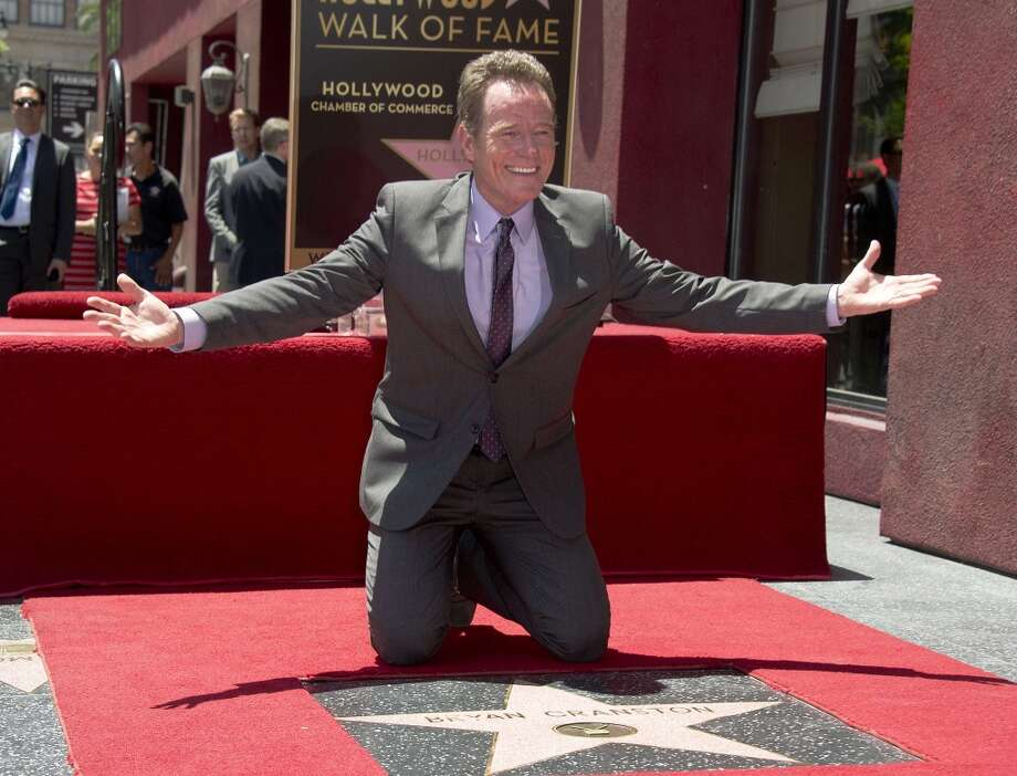 Actor Bryan Cranston poses on his star on the Hollywood Walk of Fame during the star presentation ceremony, July 16, 2013 in Hollywood, California.  AFP PHOTO / ROBYN BECKROBYN BECK/AFP/Getty Images