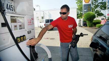 Christopher Mena pumps gas at the Shell station at the intersection of Grenhart Road and West Ave. in Stamford, Conn., on Wednesday, July 17, 2013. Mena said as a driver for Riko's Pizza he uses a lot of gas and higher prices means all of his hourly pay is spent at the pump.
