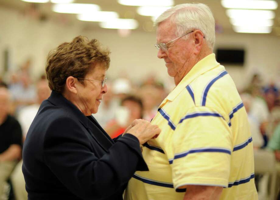 Commissioner of Veterans Affairs Linda Schwartz pins Air Force veteran Richard Austin, of Milford, with the Connecticut Veterans Wartime Service Medal Wednesday, July 17, 2013 during a ceremony at the Milford Senior Center to honor veterans of foreign wars for their bravery and service. Photo: Autumn Driscoll / Connecticut Post