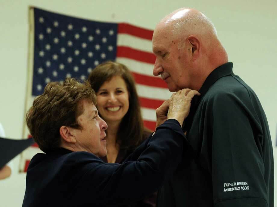 Commissioner of Veterans Affairs Linda Schwartz pins Army veteran Daniel Howrath, of Milford, with the Connecticut Veterans Wartime Service Medal Wednesday, July 17, 2013 during a ceremony at the Milford Senior Center to honor veterans of foreign wars for their bravery and service. Photo: Autumn Driscoll / Connecticut Post