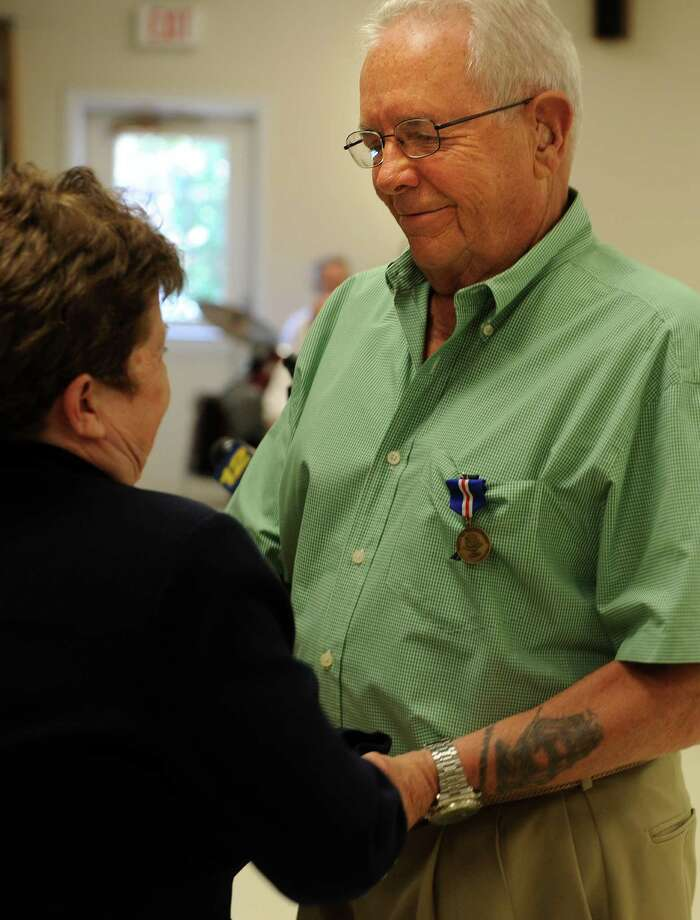 Commissioner of Veterans Affairs Linda Schwartz shakes hands with Navy veteran William Laucks, of West Haven, after pinning him with the Connecticut Veterans Wartime Service Medal Wednesday, July 17, 2013 during a ceremony at the Milford Senior Center to honor veterans of foreign wars for their bravery and service. Photo: Autumn Driscoll / Connecticut Post