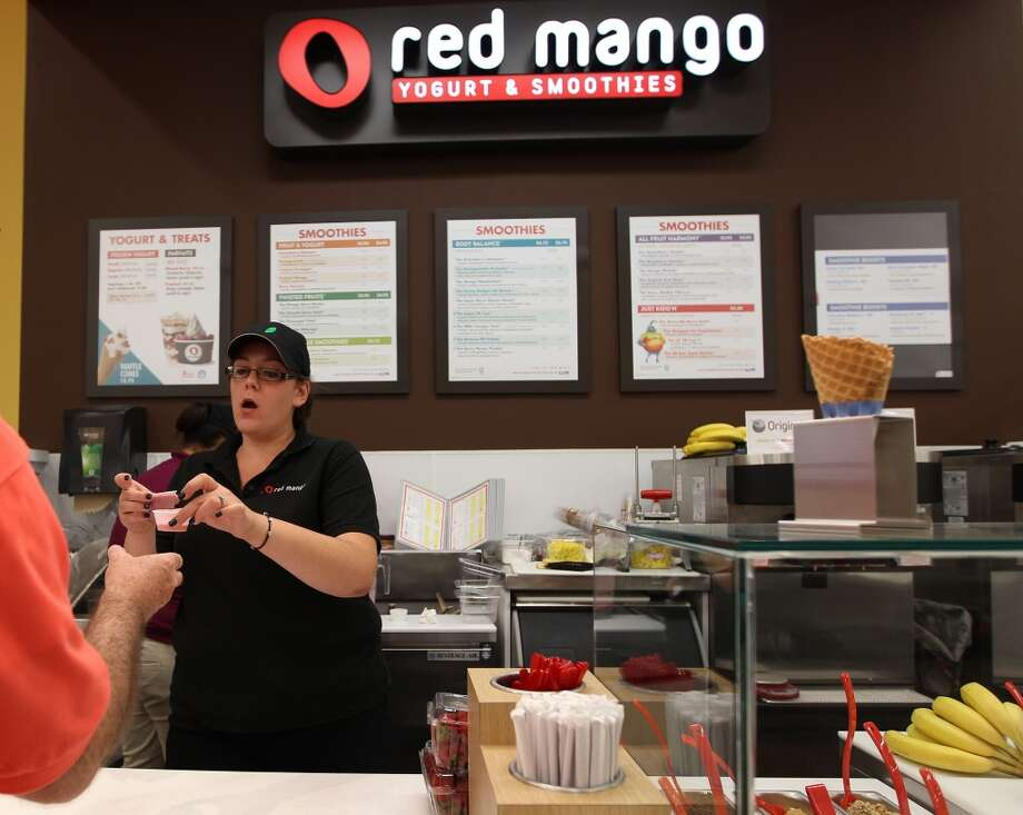 Michelle Lacqua hands a customer a sample of the Red Mango Yogurt and Smoothies during the grand opening of the Fiesta Market Place at 13833 Southwest Freeway, Wednesday, July 17, 2013, in Houston.  This new Fiesta Market Place in Sugar Creek will offer a number of firsts for a Fiesta store.( Karen Warren / Houston Chronicle )