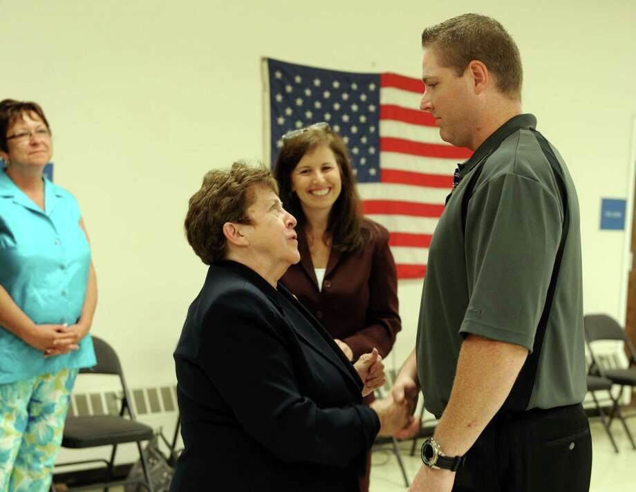 Commissioner of Veterans Affairs Linda Schwartz shakes hands with Navy veteran John McCormick, of West Haven, after pinning him with the Connecticut Veterans Wartime Service Medal Wednesday, July 17, 2013 during a ceremony at the Milford Senior Center to honor veterans of foreign wars for their bravery and service. Photo: Autumn Driscoll / Connecticut Post