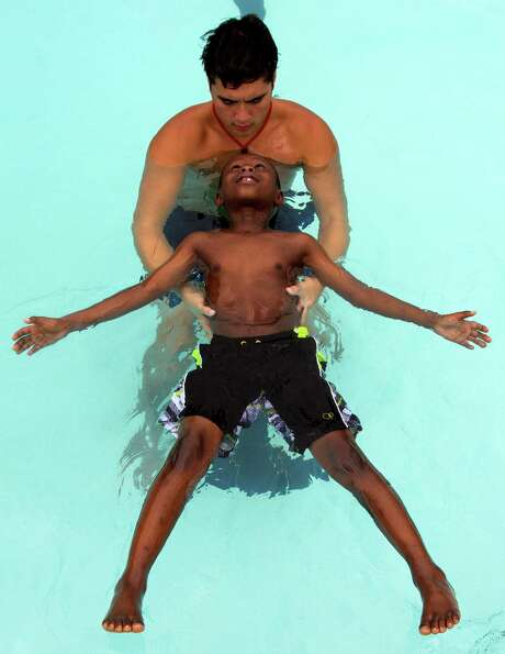 Swim instructor Jay Hong teaches Rotimi Awolola, 7, how to float during swim lessons at the Alief YMCA on Monday, July 8, 2013, in Houston.  (J. Patric Schneider / For the Chronicle ) Photo: J. Patric Schneider, Freelance / © 2013 Houston Chronicle
