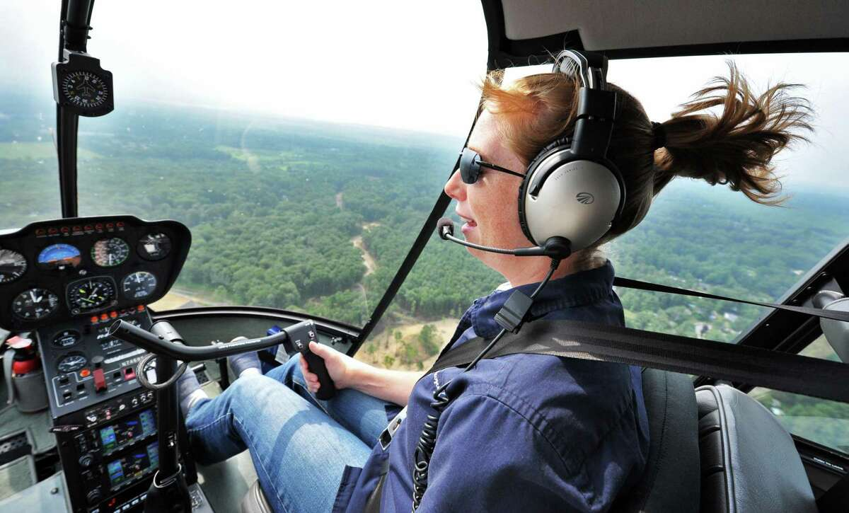 Pilot Heather Howley of Independent Helicopters flyies her Robinson R44 helicopter over Saratoga Springs, NY Wednesday July 10, 2013. (John Carl D'Annibale / Times Union)
