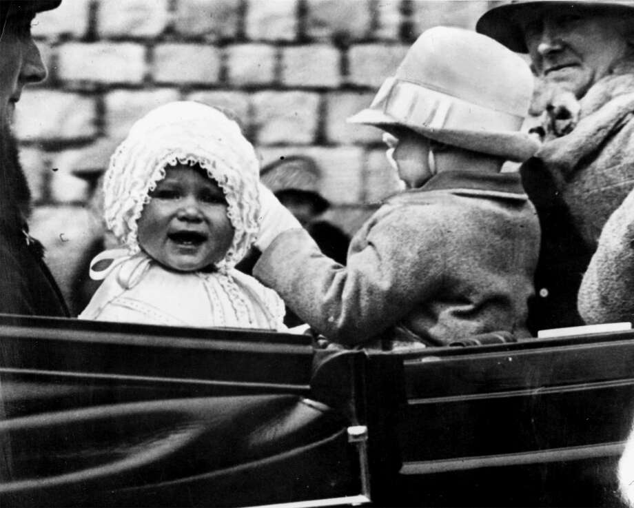 FILE -- Britain's Queen Elizabeth II, left, is seen in this 1927 file photo when she was Princess Elizabeth, aged exactly one year. The picture was made as the baby princess was taken for a ride in the grounds of Windsor Castle, she is seen with her cousin, the honourable Gerald Lascelles, right, son of Princess Royal. Britain's Queen Elizabeth II celebrates her 75th birthday on Saturday, April 21, 2001. (AP Photo/Fls/1927, file) / AP ARCHIV