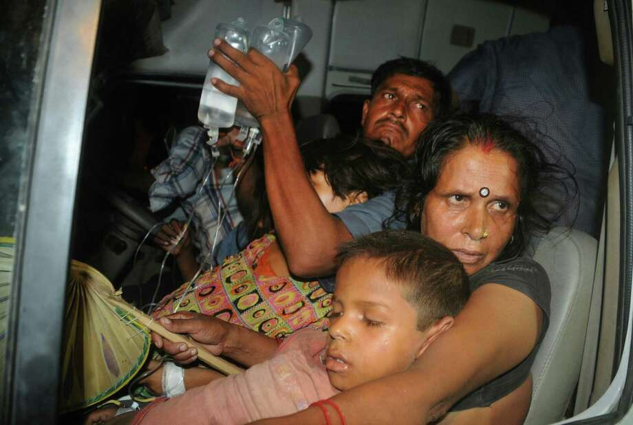 An Indian couple, with their son who fell ill Tuesday after consuming a free school meal, arrive at a hospital in Patna. Twenty-two students died after eating the lunch, and three were in serious condition. Photo: STR, Stringer / AFP