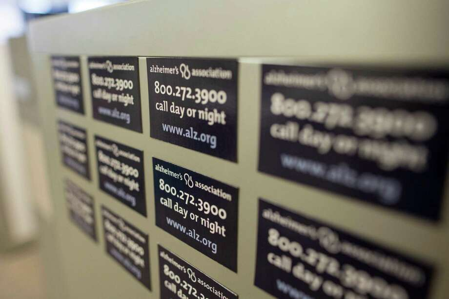 """This Friday, June 21, 2013 photo shows magnets on a cabinet at the Alzheimer's Association Headquarters in Chicago advertising their help line. Doctors often regard people who complain that their memory is slipping as """"the worried well,"""" but the new studies show they may well have reason to worry, said Maria Carrillo, a senior scientist at the Alzheimer's Association. (AP Photo/Scott Eisen) Photo: Scott Eisen, STF / AP"""