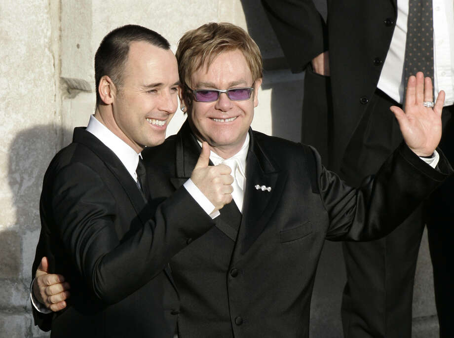 FILE - This is a Wednesday Dec. 21, 2005 file photo of pop star Elton John, right, and his longtime partner David Furnish, embrace as they wave to members of the media and the public after they had a civil ceremony at the Guildhall  in the town of Windsor, England  John and Furnish were the most prominent of hundreds of same-sex couples planning to form civil partnerships in England and Wales on Wednesday, the first day that such ceremonies become possible. With little fanfare or controversy, Britain announced Wednesday July 17, 2013 that Queen Elizabeth II _ hardly a social radical _ had signed into law a bill legalizing same-sex marriages in England and Wales. France has also legalized gay marriages, but only after a series of gigantic protests attracting families from the traditional heartland that revealed a deeply split society. (AP Photo/Lefteris Pitarakis) Photo: LEFTERIS PITARAKIS, STF / AP