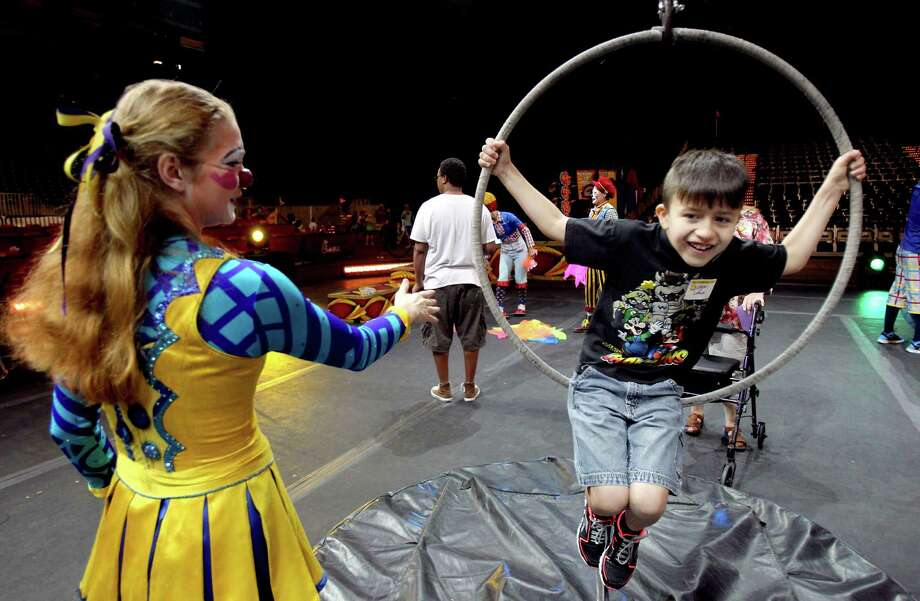 Clowns supervise as student Logan Loredo learns how to balance on ahoop. Sunshine Kids are learning clown skills during the Clown Jr. College three day camp at Reliant Stadium on Wednesday, July 17, 2013, in Houston.  The Sunshine Kids Foundation campers will perform in the All-Access PreShow of the Ringling Bros. and Barnum & Bailey Circus on July 24th. Photo: Mayra Beltran / © 2013 Houston Chronicle