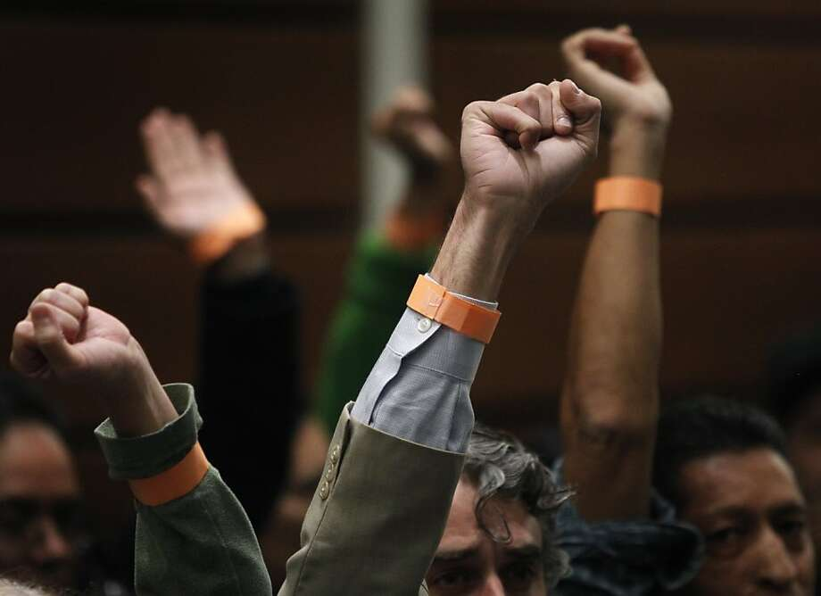 UCSF employees raise their fists during the regents meeting to demand improved safety measures at USCF Medical Center. Photo: Paul Chinn, The Chronicle