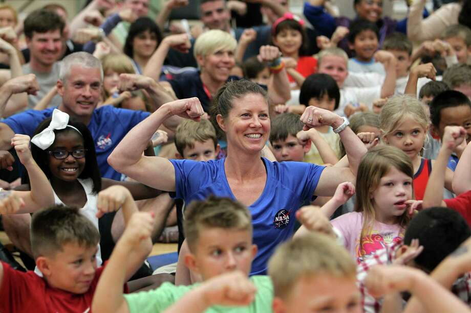 NASA astronaut Tracy Caldwell Dyson pose for a photo with campers before demonstrating how they get fit for space at Johnson Space Center, on Wednesday, July 17, 2013, in Houston. Photo: Mayra Beltran / © 2013 Houston Chronicle