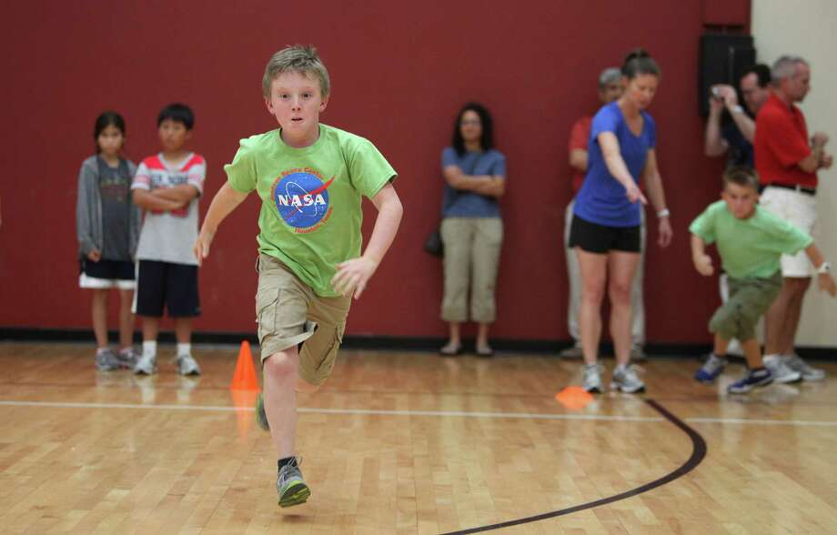 Taylor Stewart, 10, sprints to finish a relay in the group taught by NASA astronaut Tracy Caldwell Dyson as campers learn how to get fit for space at Johnson Space Center on Wednesday, July 17, 2013, in Houston. Photo: Mayra Beltran / © 2013 Houston Chronicle