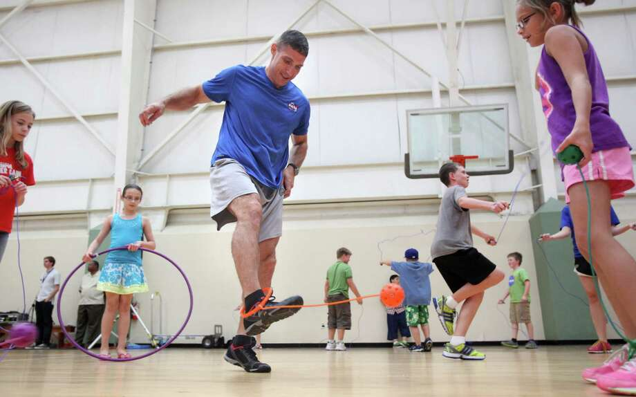 NASA astronaut Mike Hopkins attempts to jump with camper's toys while they learn how astronauts get physically ready to work in space at Johnson Space Center on Wednesday, July 17, 2013, in Houston. Photo: Mayra Beltran / © 2013 Houston Chronicle