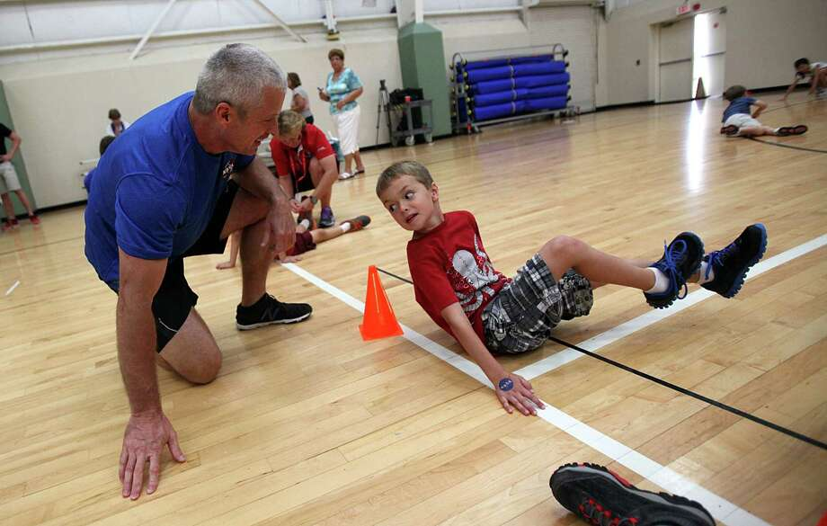 NASA astronaut Steve Swanson waits to be tagged out by relay partner Ewan Schwanbeck, 6, while campers learn how to get fit for space at Johnson Space Center, on Wednesday, July 17, 2013, in Houston. Photo: Mayra Beltran / © 2013 Houston Chronicle