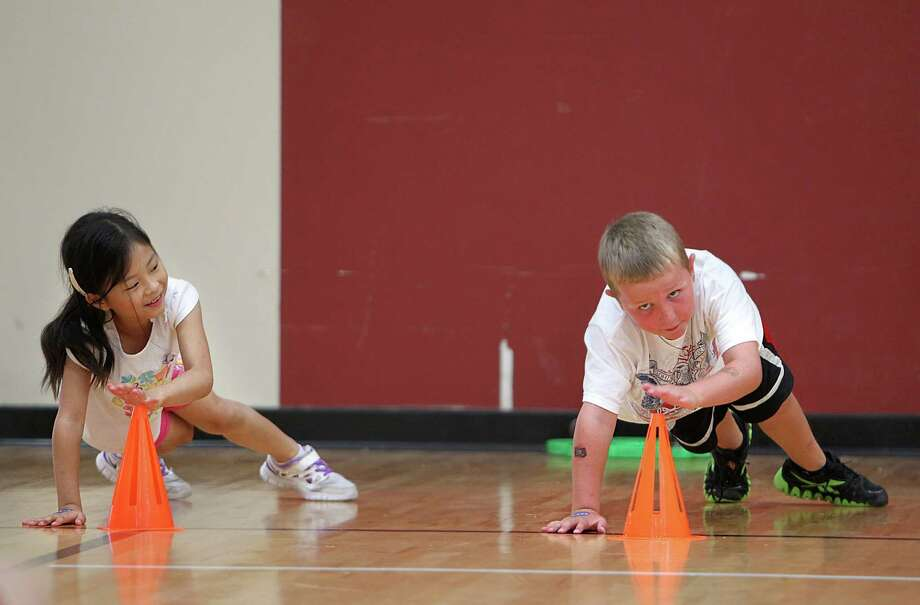 Wen-Yuan Wu, 6, tries to finish exercises while Austin Dahms, 7, looks up for his partner during a relay routine at Johnson Space Center, on Wednesday, July 17, 2013, in Houston. NASA astronauts taught campers how to get fit for space. Photo: Mayra Beltran / © 2013 Houston Chronicle