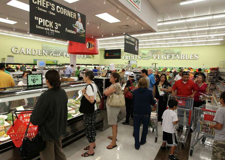 Customers line up at the chef's station during the grand opening of the Fiesta Market Place in the Sugar Land area on U.S. 59. The station offers breakfast, lunch and dinner items as well as a hot food bar and sushi.  ON THE Southwest Freeway, Wednesday, July 17, 2013, in Houston.  This new Fiesta Market Place in Sugar Creek will offer a number of firsts for a Fiesta store.( Karen Warren / Houston Chronicle ) Photo: Karen Warren, Staff / © 2013 Houston Chronicle