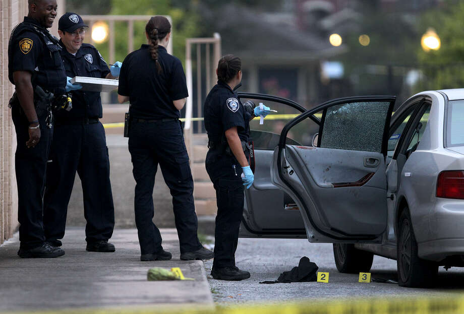 San Antonio police investigate a crime scene in a parking lot near Bandera Road at East Sunshine Drive, where a group of teens drove after one of them was shot in the head at a nearby apartment complex. Photo: John Davenport / San Antonio Express-News