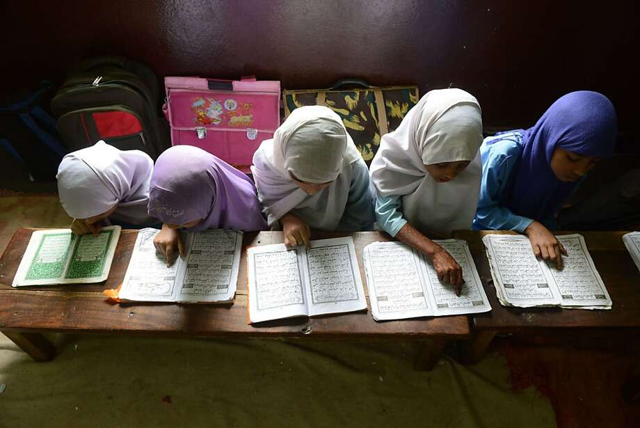 Indian Muslim girls recite the Holy Quran in their class room during the holy month of Ramadan at Madrasatur-Rashaad religious school in Hyderabad on July 17, 2013.  As well as abstinence and fasting during Ramadan, Muslims are encouraged to pray and read the Quran during Islam's holiest month.  AFP PHOTO / Noah SEELAMNOAH SEELAM/AFP/Getty Images Photo: Noah Seelam, AFP/Getty Images
