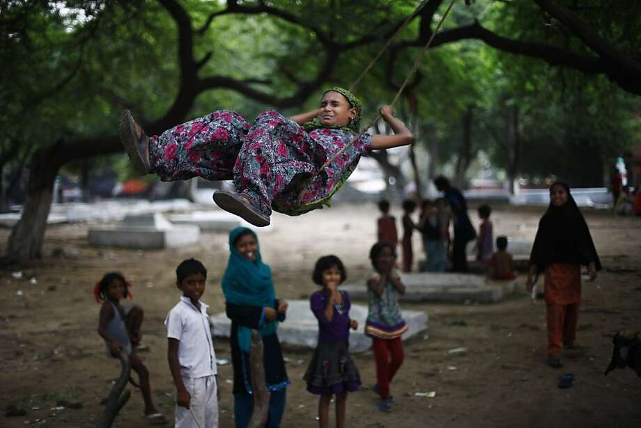 A young Indian Muslim girl reacts during a swing ride in New Delhi, India, Wednesday, July 17, 2013. (AP Photo/Altaf Qadri) Photo: Altaf Qadri, Associated Press