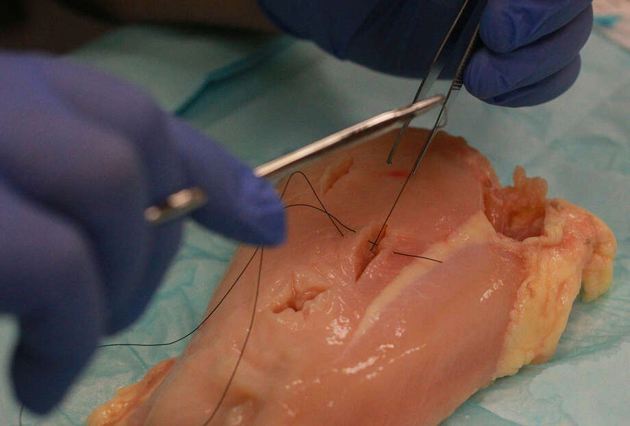 Assistant program director Dr. Salim Rezaie says chicken closely resembles human flesh for suturing practice.