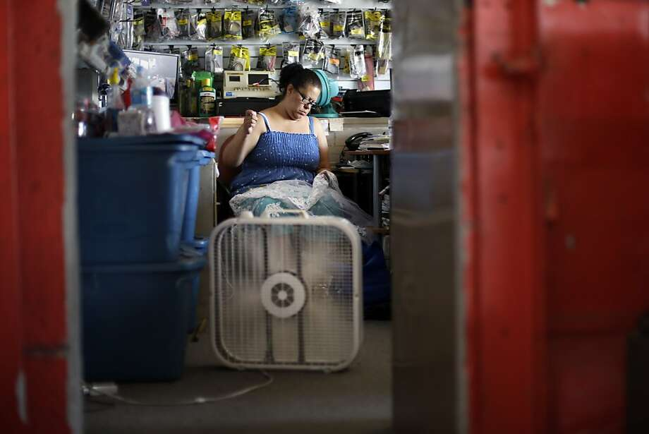 Maribel Castro sews in her un-air conditioned shop, Wednesday, July 17, 2013, in Philadelphia. An excessive heat warning is again in effect for the Philadelphia region with highs expected to head up to the mid-90s (AP Photo/Matt Rourke) Photo: Matt Rourke, Associated Press