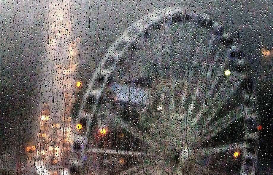 Debuting in a downpour:Raindrops splash against an office window as heavy rain and 