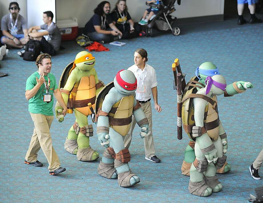 Teenage Ninja Turtle characters walk through the San Diego Convention Center during the Preview Night event on Day 1 of the 2013 Comic-Con International Convention on Wednesday, July 17, 2013, in San Diego.  (Photo by Denis Poroy/Invision/AP) Photo: Denis Poroy, Associated Press