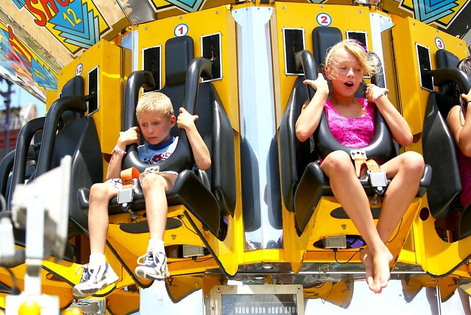 7-year-old Michael Pruitt and 11-year-old Kayla Spears, both of Watervliet, Mich. have distinctly different reactions to the ride down on the Mega Shot at the Van Buren County Youth Fair in Lawrence, Mich. on Wednesday July 17, 2013. (AP Photo/The Herald Palladium, Joe Rondone) Photo: Joe Rondone, Associated Press