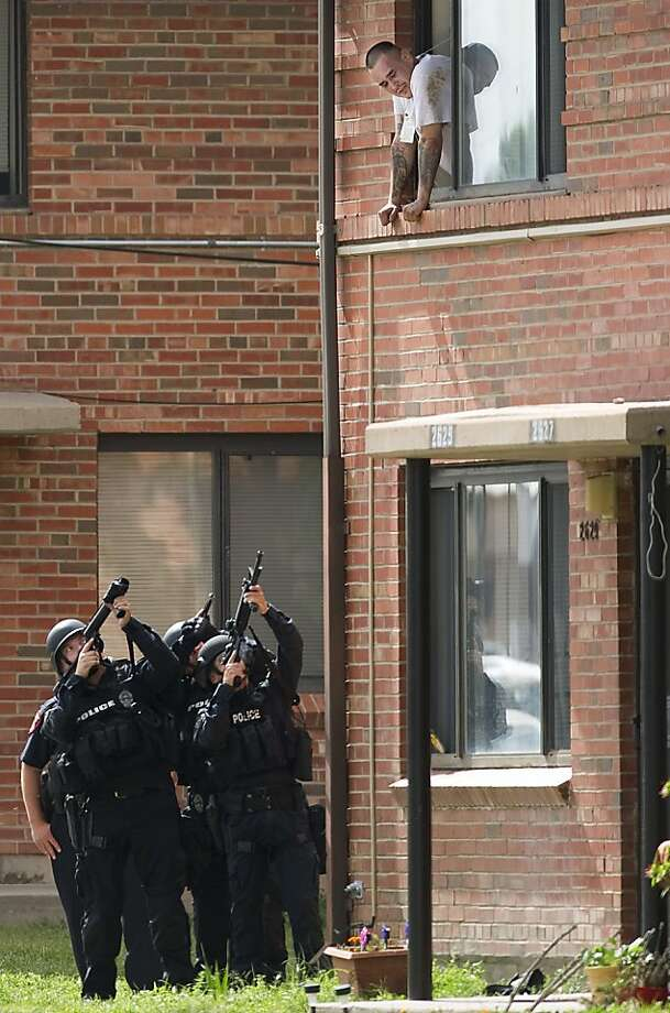 Members of the Pueblo Police Department swat team point their weapons at wanted fugitive, Ray D. Gonzales in a window of an apartment   in the Sangre de Cristo Apartments Tuesday afternoon July 16, 2013 in Pueblo, Colo. Gonzales surrendered after he talked to police from a second-story window while police kept their weapons aimed at him.    (AP Photo/The Pueblo Chieftain, Bryan Kelsen) Photo: Bryan Kelsen, Associated Press