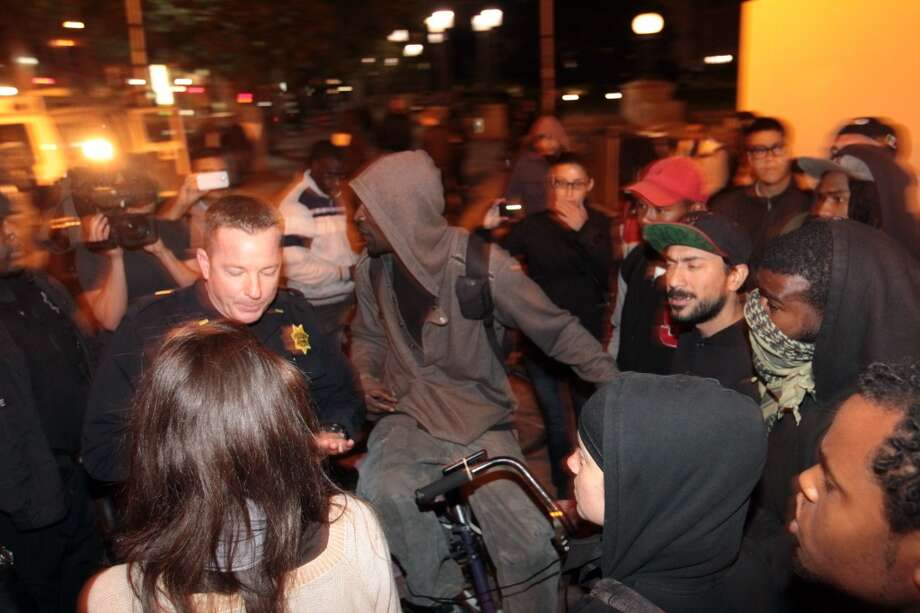 OaklandPolice move in to get a man to stop riding his bicycle on the sidewalk near 14th and Broadway on Tuesday night.