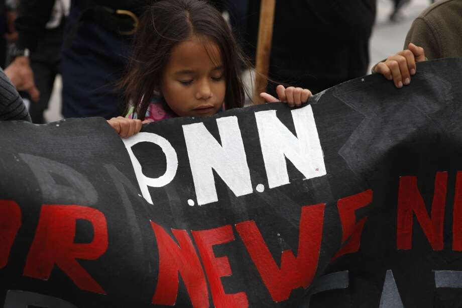 San Francisco  Luna Carrillo, 6, helps to hold a banner during during a protest against the San Francisco Police Department on the one year anniversary of the death of Kenneth Harding in San Francisco, Calif. on July 16, 2013.