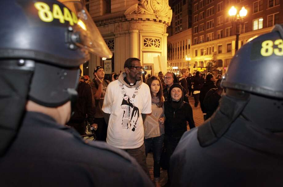 Oakland  Pastor Preston Walker tries to speak with police on the sidewalk near 14th and Broadway on Tuesday night.