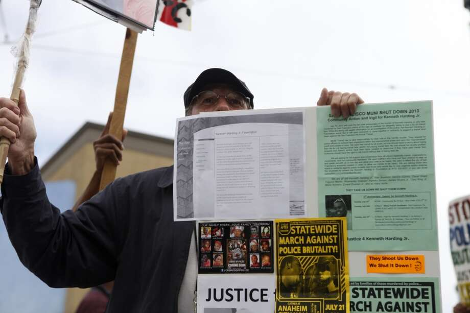 San Francisco  A protestor hold a sign and poster during a protest against the San Francisco Police Department on the one year anniversary of the death of Kenneth Harding in San Francisco, Calif. on July 16, 2013.