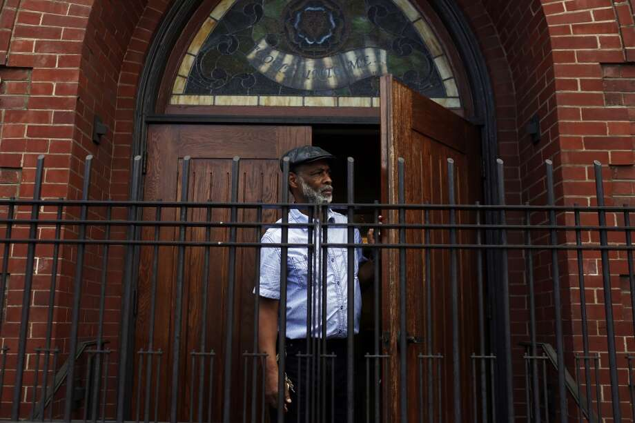 San Francisco  Clifton King peers out of a doorway to watch protestors march down Church Street during a protest against the San Francisco Police Department.
