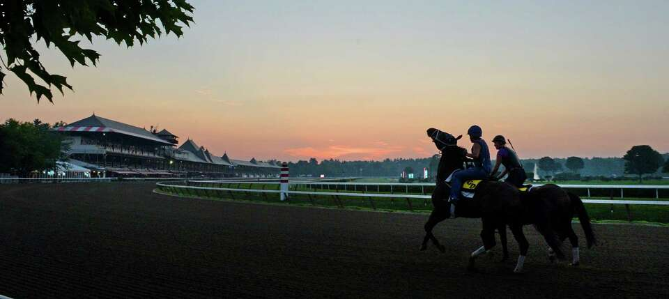 Horses trained by Glen DeSanto go out for their morning exercise as the sun rises Thursday morning,