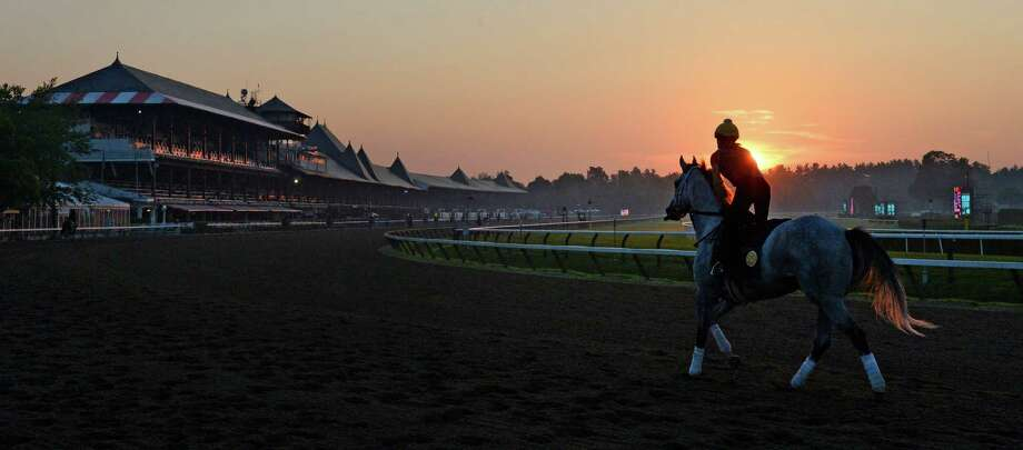 Horses go out for their morning exercise as the sun rises Thursday morning, July 18, 2013, at Saratoga Race Course in Saratoga Springs, N.Y. The 150th race meet begins Friday.  (Skip Dickstein/Times Union) Photo: SKIP DICKSTEIN / 10023138A