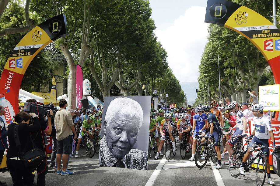 A portrait of former South African President Nelson Mandela is displayed in front of cyclists at the kilometer zero at the departure village to celebrate Mandela's birthday in Gap, before the start of the 172.5 km eighteenth stage of the 100th edition of the Tour de France cycling race on July 18, 2013 between Gap and Alpe-d'Huez, French Alps. Photo: PASCAL GUYOT, AFP/Getty Images / 2013 AFP